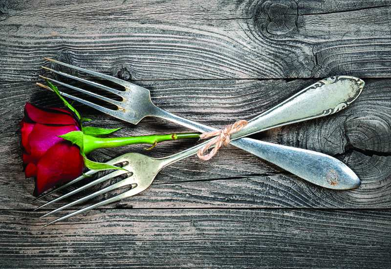 two forks with a rose in between them