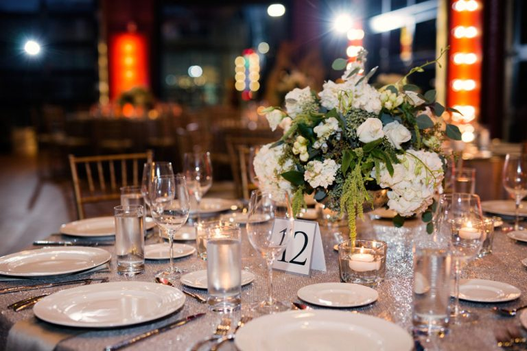 table #12, with glasses, plates, and a white flower centerpiece